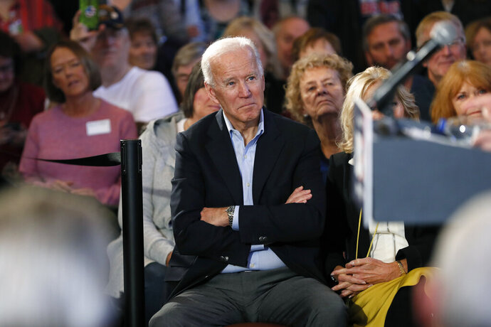 Democratic presidential candidate former Vice President Joe Biden waits to speak to local residents during a bus tour stop, Tuesday, Dec. 3, 2019, in Mason City, Iowa. (AP Photo/Charlie Neibergall)
