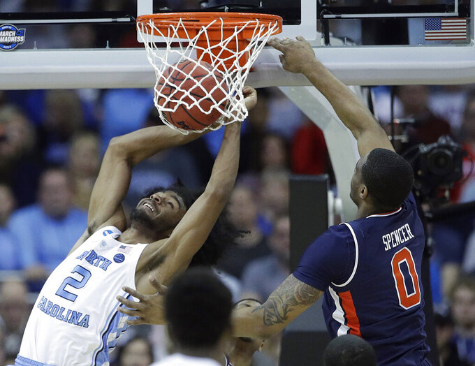 North Carolina's Coby White (2) dunks as Auburn's Horace Spencer (0) defends during the second half of a men's NCAA tournament college basketball Midwest Regional semifinal game Friday, March 29, 2019, in Kansas City, Mo. (AP Photo/Charlie Riedel)