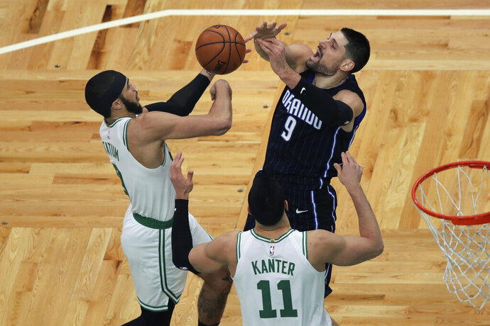 Orlando Magic center Nikola Vucevic (9) and Boston Celtics forward Jayson Tatum (0) vie for a rebound during the first quarter of an NBA basketball game in Boston, Wednesday, Feb. 5, 2020. (AP Photo/Charles Krupa)