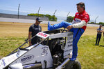 Jeff Gordon, a five-time winner of the Brickyard 400 and four-time NASCAR Cup Series champion, climbs into a USAC midget car before taking some exhibition laps on the dirt track in the infield at Indianapolis Motor Speedway in Indianapolis, Thursday, June 17, 2021. (AP Photo/Michael Conroy)