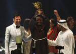 Kenyan teacher Peter Tabichi, center, actor Hugh Jackman, left, and Dubai crown prince Sheikh Hamdan bin Mohammed Al Maktoum, right, react after Tabichi won the $1 million Global Teacher Prize in Dubai, United Arab Emirates, Sunday, March 24, 2019. Tabichi is a science teacher who gives away 80 percent of his income to the poor in the remote Kenyan village of Pwani. (AP Photo/Jon Gambrell)