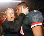FILE - In this Dec. 30, 1998, file photo, Arizona coach Dick Tomey, left, congratulates linebacker DaShon Polk after the Wildcats 23-20 win over Nebraska in the Holiday Bowl NCAA college football game in San Diego. Tomey, the winningest football coach in University of Arizona history, died Friday night, May 10, 2019, in Tucson, Ariz. He was 80. Tomey was 183-145-7 overall in 20 years as head coach at Hawaii, Arizona and San Jose State. He was diagnosed with lung cancer in December.  (AP Photo/Denis Poroy, File)
