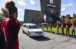 St. John's University, Minn., football players line the road as long time St. John's University football coach John Gagliardi passes in a hearse Monday, Oct. 15, 2018, at the St. John's Abbey in Collegeville, Minn. (Jason Wachter/St. Cloud Times via AP)