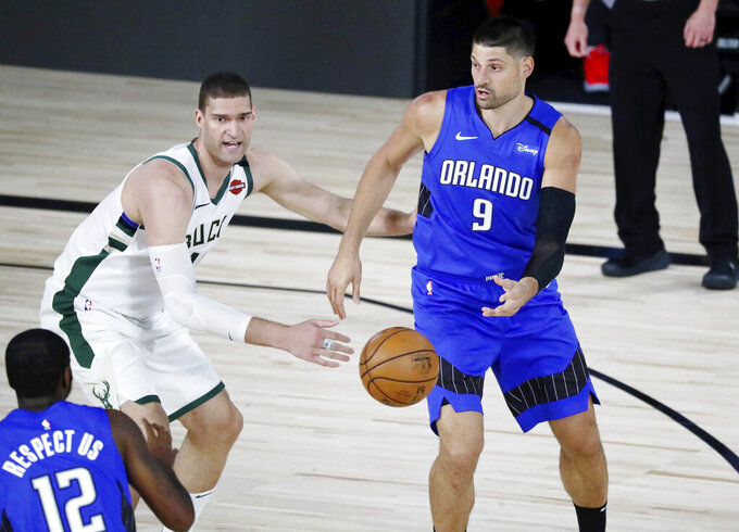 Orlando Magic center Nikola Vucevic (9) passes the ball to forward Gary Clark (12) in front of Milwaukee Bucks center Brook Lopez (11) during the first half of Game 1 of an NBA basketball first-round playoff series, Tuesday, Aug. 18, 2020, in Lake Buena Vista, Fla. (Kim Klement/Pool Photo via AP)