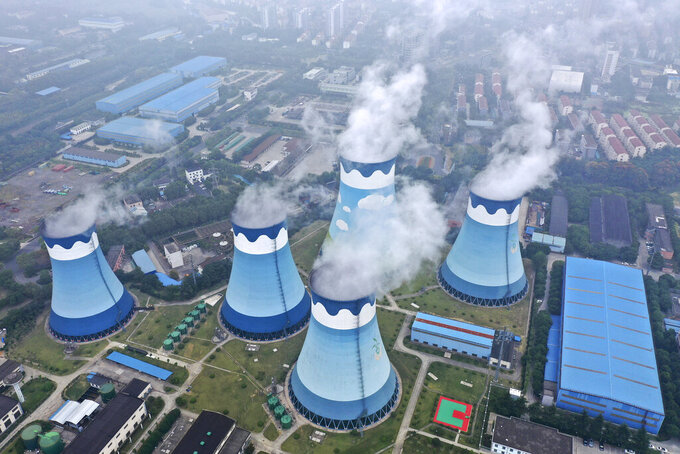 Steam billows out of the cooling towers at a coal-fired power station in Nanjing in east China's Jiangsu province on Monday, Sept. 27, 2021. Global shoppers face possible shortages of smartphones and other goods ahead of Christmas after power cuts to meet government energy use targets forced Chinese factories to shut down and left some households in the dark. (Chinatopix via AP)