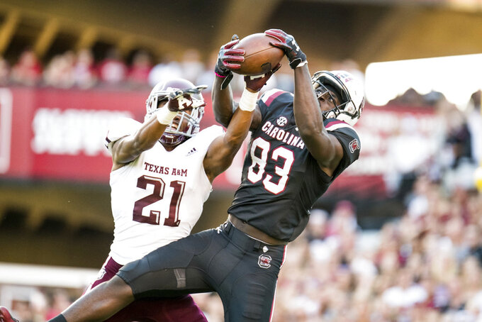 South Carolina wide receiver Chavis Dawkins (83) catches a touchdown pass against Texas A&M defensive back Charles Oliver (21) during the second half of an NCAA college football game Saturday, Oct. 13, 2018, in Columbia, S.C. Texas A&M defeated South Carolina 26-23. (AP Photo/Sean Rayford)