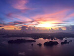 The sun sets over outlying islands as a plane prepares to land on the resort island of Phuket, Thailand on Wednesday, May 22, 2019. Thailand hopes to first fully reopen the island of Phuket, its most popular destination, by July 1 for vaccinated visitors without quarantine. But they will be required to spend a certain time, possibly up to a week, on Phuket before they are allowed to travel elsewhere in Thailand. (AP Photo/Adam Schreck)