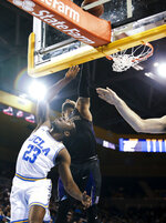 Washington guard David Crisp, top, blocks a shot by UCLA guard Prince Ali during the second half of an NCAA college basketball game in Los Angeles, Sunday, Dec. 31, 2017. UCLA won 74-53. (AP Photo/Ringo H.W. Chiu)