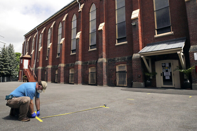A worker marks socially distanced spots in a parking lot for parishioners, due to the coronavirus outbreak, outside St. Rose of Lima Catholic Church in Chelsea, Mass., Friday, May 29, 2020. Masses, which were stopped in March due to fears of spreading the coronavirus, will resume this weekend. (AP Photo/Charles Krupa)