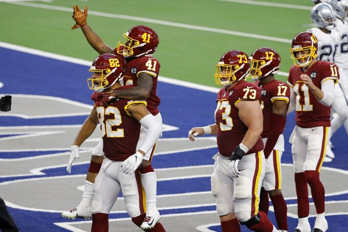 Washington Football Team's Logan Thomas (82) and J.D. McKissic (41) celebrate McKissic's touchdown as Chase Roullier (73), Terry McLaurin (17) and Alex Smith (11) look on during the first half of the team's NFL football game against the Dallas Cowboys in Arlington, Texas, Thursday, Nov. 26, 2020. (AP Photo/Ron Jenkins)
