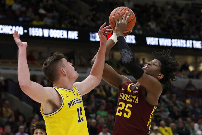 Michigan's Jon Teske (15) blocks a shot by Minnesota's Daniel Oturu (25) during the first half of an NCAA college basketball game in the semifinals of the Big Ten Conference tournament, Saturday, March 16, 2019, in Chicago. (AP Photo/Nam Y. Huh)