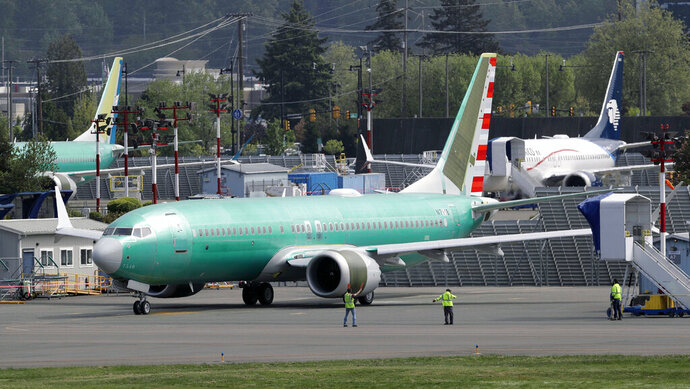 FILE - In this Wednesday, May 8, 2019 file photo, workers stand near a Boeing 737 MAX 8 jetliner being built for American Airlines prior to a test flight in Renton, Wash. Federal safety officials are recruiting pilots from airlines around the world to test changes that Boeing is making in flight-control software on the grounded 737 Max jet, according to two people briefed on the situation (AP Photo/Ted S. Warren, File)