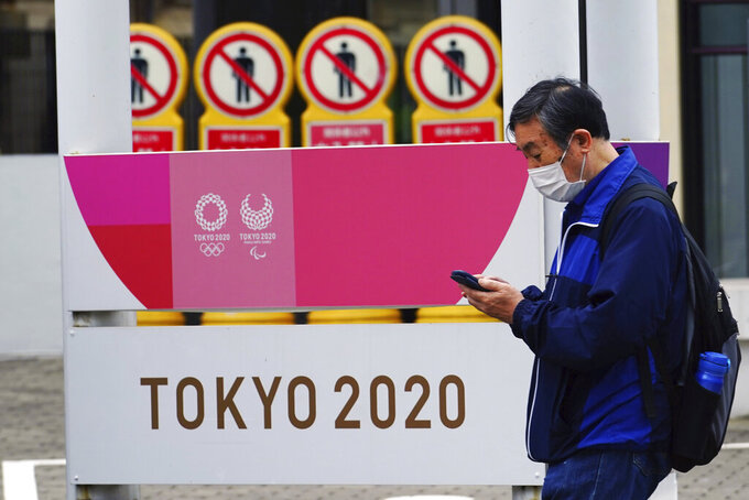 A man wearing a protective mask to help curb the spread of the coronavirus walks past a banner for the Tokyo 2020 Olympic and Paralympic Games in Tokyo Tuesday, May 11, 2021. The Japanese capital confirmed more than 920 new coronavirus cases on Tuesday. (AP Photo/Eugene Hoshiko)