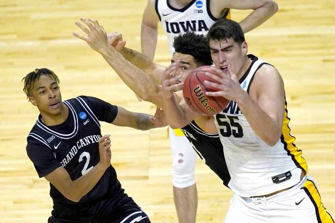 Iowa's Luka Garza (55) bobbles a pass as Grand Canyon's Chance McMillian (2) and Gabe McGlothan defend during the first half of a first round NCAA college basketball tournament game Saturday, March 20, 2021, at the Indiana Farmers Coliseum in Indianapolis. (AP Photo/Charles Rex Arbogast)