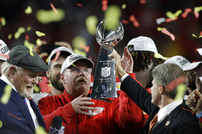 FILE - In this Feb. 2, 2020, file photo, Kansas City Chiefs chairman Clark Hunt, right, hands the trophy to head coach Andy Reid after the chiefs defeated the San Francisco 49ers in the NFL Super Bowl 54 football game in Miami Gardens, Fla. It's hard enough when things are normal — only seven franchises have won back-to-back championships. But it's even more difficult when the offseason has been thrown into turmoil because of the coronavirus pandemic, affecting everything from free agency to the NFL draft to team workouts that should have begun this month, but will not. (AP Photo/Chris O'Meara, File)