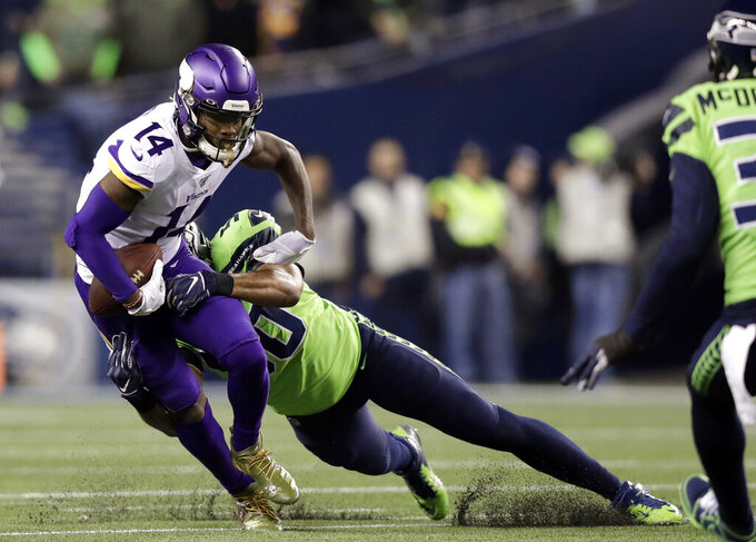 Seattle Seahawks' K.J. Wright, center, tackles Minnesota Vikings' Stefon Diggs (14) during the first half of an NFL football game, Monday, Dec. 2, 2019, in Seattle. (AP Photo/John Froschauer)