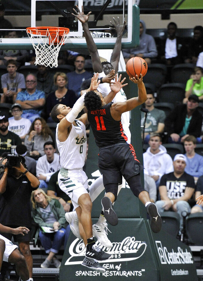 South Florida's David Collins (0) and Mayan Kiir, right, block a shot from Houston guard Nate Hinton (11) during the first half of a NCAA college basketball game Saturday, Jan. 19, 2019 in Tampa, Fla. (AP Photo/Steve Nesius)