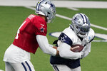 Dallas Cowboys quarterback Dak Prescott (4) hands off to running back Ezekiel Elliott during an NFL football training camp in Frisco, Texas, Monday, Aug. 24, 2020. (AP Photo/LM Otero)