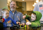 In this Friday, Feb. 16, 2018 photo, Francisco, 2, and Tucker, 4, play as their dad, Jay, is interviewed in their home in Grand Rapids, Mich. The Schwandt family has 13 sons and have welcomed a 14th into the family. The couple's latest addition was born Wednesday evening, April 18 five days before the baby's expected due date. (Casey Sykes /The Grand Rapids Press via AP)