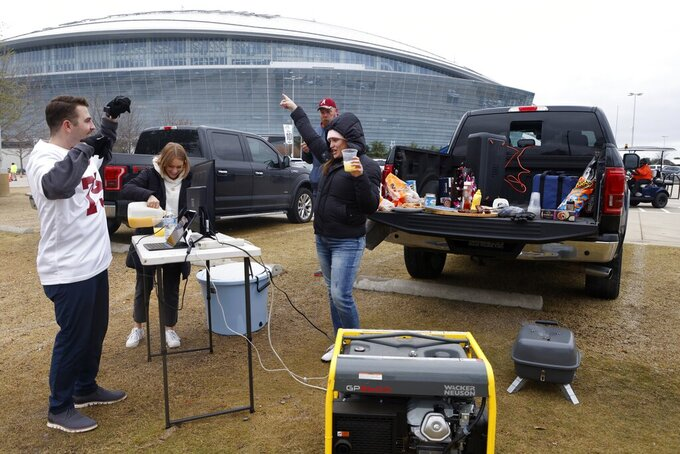 Alabama fans tailgate outside AT&T Stadium before the Rose Bowl NCAA college football game against Notre Dame in Arlington, Texas, Friday, Jan. 1, 2021. (AP Photo/Michael Ainsworth)