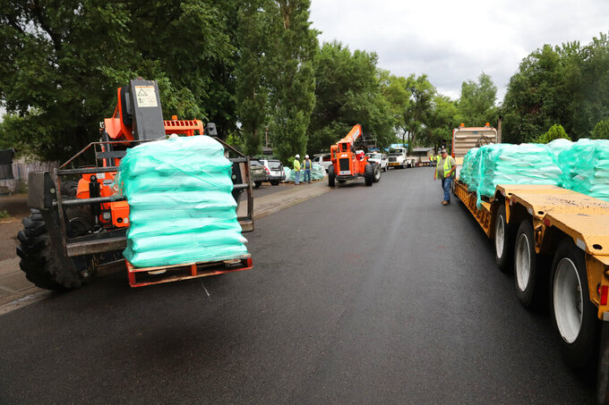 Sandbags are unloaded onto Main Street in the Sunnyside section of Flagstaff, Ariz. in 2019 as crews work to protect individual homes from potential floodwaters in the Museum Fire burn area. It's nearly two years since a fire burned nearly 2,000 acres in hills north of Flagstaff but rows of concrete barriers and stacks of sandbags remain in place in neighborhoods along a wash that runs down into the city. (Jake Bacon/Arizona Daily Sun via AP)