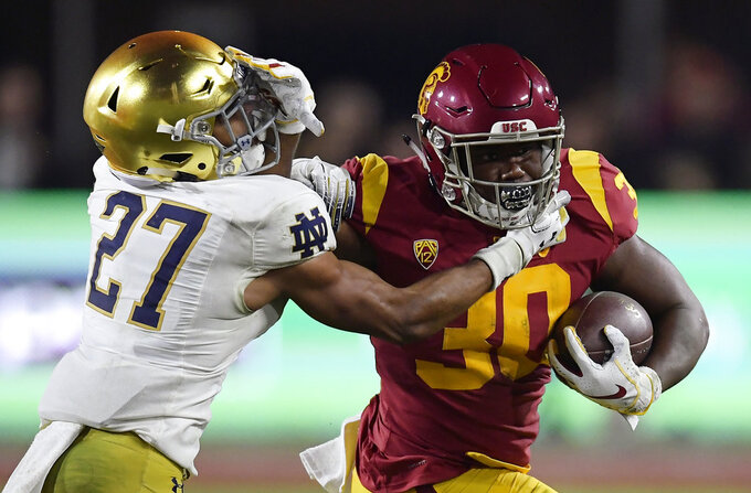 Southern California running back Markese Stepp, right, fends off Notre Dame cornerback Julian Love during the second half of an NCAA college football game Saturday, Nov. 24, 2018, in Los Angeles. Notre Dame won 24-17. (AP Photo/Mark J. Terrill)