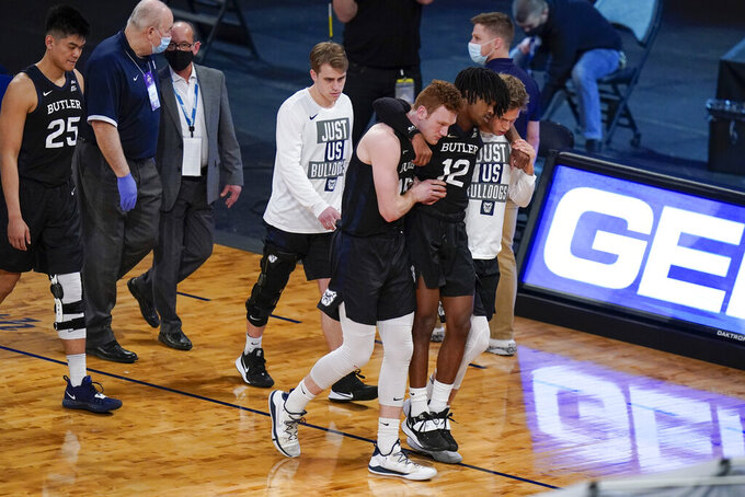 Butler's Myles Tate (12) is carried to the bench by teammates after he was hurt during the second half of an NCAA college basketball game against Creighton in the Big East conference tournament Thursday, March 11, 2021, in New York. (AP Photo/Frank Franklin II)