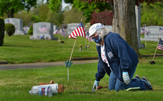 Carolyn Lauer takes a break from tending a gravestone to talk with her sister Nancy Kissinger, Wednesday, May 20, 2020, at Calvary Cemetery in Millcreek Township, Erie County, Pennsylvania. The siblings were cleaning family grave markers in advance of Memorial Day. While doing the annual work, Lauer, 67, of Lawrence Park Township, Erie County, wore an American flag-themed face mask that she made herself.
