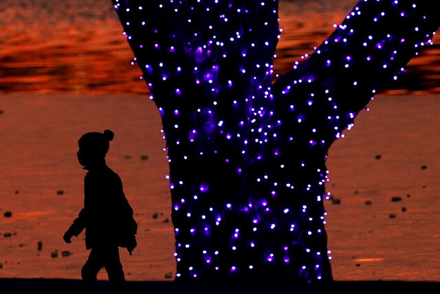 A boy wears masks to prevent the spread of the coronavirus as he looks at a holiday display on a mild day Saturday, Dec. 26, 2020, in a park in Lenexa, Kan. (AP Photo/Charlie Riedel)