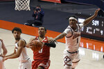 Wisconsin's guard D'Mitrik Trice goes to the basket as Illinois guards Trent Frazier (1) and Jacob Grandison defends in the first half of an NCAA college basketball game Saturday, Feb. 6, 2021, in Champaign, Ill. (AP Photo/Holly Hart)