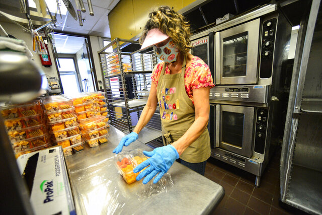 Pam Kissell, a food service worker at the Bellows Falls Union High School, in Westminster, Vt., wraps meals to be handed out to students as part of the Windham Northeast Supervisory Union summer meals program on Friday, Aug. 7, 2020. (Kristopher Radder/The Brattleboro Reformer via AP)