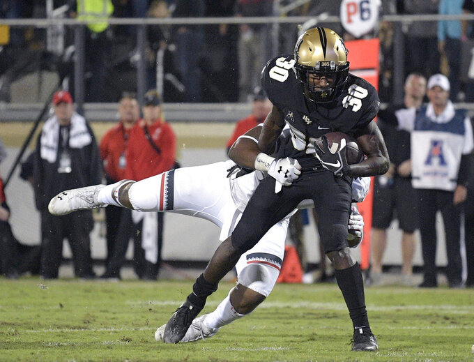 Central Florida running back Greg McCrae (30) rushes for a 9-yard touchdown in front of Cincinnati defensive end Malik Vann during the second half of an NCAA college football game Saturday, Nov. 17, 2018, in Orlando, Fla. Central Florida won, 38-13. (AP Photo/Phelan M. Ebenhack)
