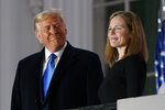 President Donald Trump and Amy Coney Barrett stand on the Blue Room Balcony after Supreme Court Justice Clarence Thomas administered the Constitutional Oath to her on the South Lawn of the White House White House in Washington, Monday, Oct. 26, 2020. Barrett was confirmed to be a Supreme Court justice by the Senate earlier in the evening. (AP Photo/Patrick Semansky)