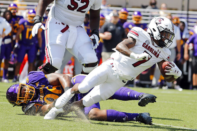 South Carolina's Ahmarean Brown (7) gets tripped up by East Carolina's D'Angelo McKinnie (96) during the first half of an NCAA college football game in Greenville, N.C., Saturday, Sept. 11, 2021. (AP Photo/Karl B DeBlaker)
