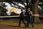 FILE - In this March 20, 2019, file photo, police officers patrol at a park outside the Al Noor mosque in Christchurch, New Zealand. On March 15, 2019, a gunman allegedly fueled by anti-Muslim hatred attacked two mosques in Christchurch, killing 51 people.  (AP Photo/Vincent Yu, File)