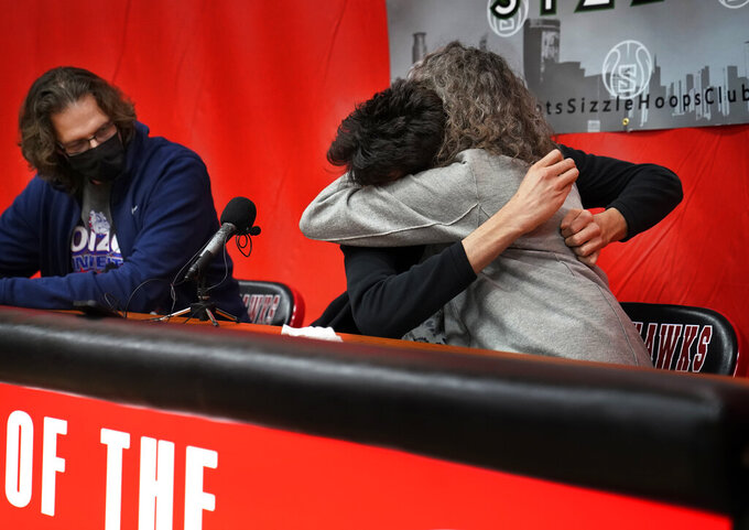 Minnehaha Academy's Chet Holmgren, center, the No. 1 NCAA college basketball recruit in the country, hugs his mother Sarah Harris as his father, David Holmgren looks on after revealing he will be attending Gonzaga University to play basketball during a press conference in Minneapolis, Monday, April 19, 2021.  (David Joles/Star Tribune via AP)