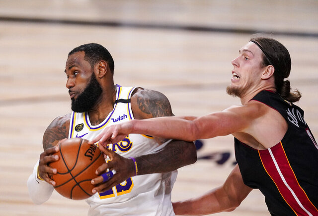 Los Angeles Lakers' LeBron James (23) and Miami Heat's Kelly Olynyk (9) fight for control fo the ball during the first half in Game 3 of basketball's NBA Finals, Sunday, Oct. 4, 2020, in Lake Buena Vista, Fla. (AP Photo/Mark J. Terrill)