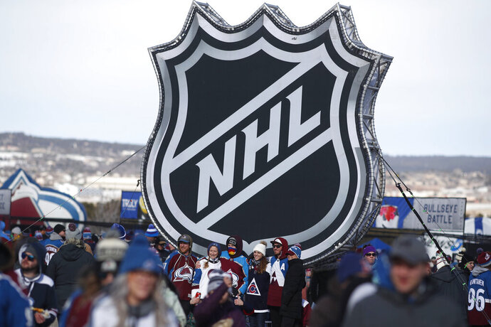 FILE - In this Feb. 15, 2020, file photo, fans pose below the NHL league logo at a display outside Falcon Stadium before an NHL Stadium Series outdoor hockey game between the Los Angeles Kings and Colorado Avalanche, at Air Force Academy, Colo. The uncertainty raised by coronavirus pandemic leads to experts providing a bleak short-term assessment on the NHL's financial bottom line, with some projecting revenues being cut by almost half. What's unclear is how large the impact might be until it can be determined when fans can resume attending games and if the league is able to complete this season. (AP Photo/David Zalubowski, File)