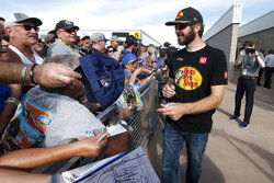 Driver Martin Truex Jr., front right, gives autographs to fans prior to a NASCAR Cup Series auto race at ISM Raceway, Sunday, Nov. 10, 2019, in Avondale, Ariz. (AP Photo/Ralph Freso)