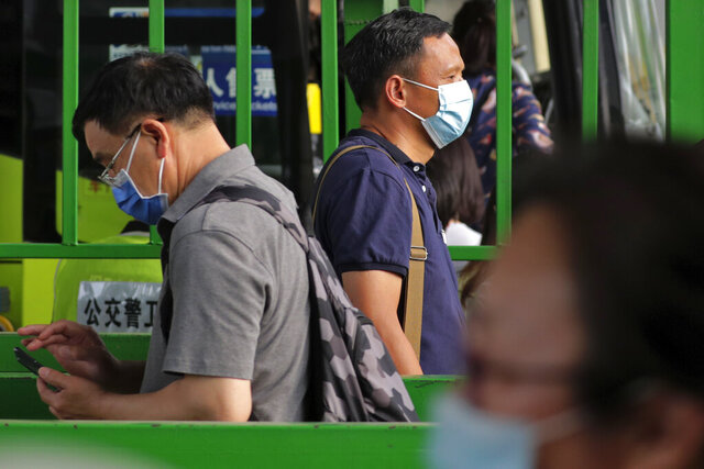 Commuters wearing protective face masks to help curb the spread of the new coronavirus line up to board a bus at a bus terminal in Beijing, Monday, June 22, 2020. A Beijing government spokesperson said the city has contained the momentum of a recent coronavirus outbreak that has infected a few hundreds of people, after the number of daily new cases fell to single digits. (AP Photo/Andy Wong)