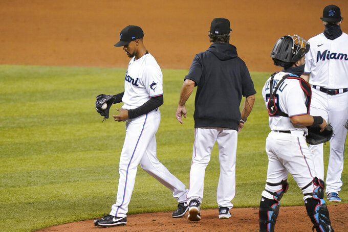 Miami Marlins relief pitcher Stephen Tarpley, left, walks from the mound as he is relieved during the eighth inning of a baseball game New York Mets, Tuesday, Aug. 18, 2020, in Miami. (AP Photo/Lynne Sladky)