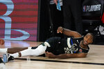 Milwaukee Bucks' Khris Middleton (22) goes down during the second half of an NBA conference semifinal playoff basketball game against the Miami Heat Wednesday, Sept. 2, 2020, in Lake Buena Vista, Fla. The Heat won 116-114. (AP Photo/Mark J. Terrill)