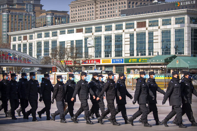 Policemen wear face masks as they march in formation outside the Beijing Railway Station in Beijing, Saturday, Feb. 15, 2020. People returning to Beijing will now have to isolate themselves either at home or in a concentrated area for medical observation, said a notice from the Chinese capital's prevention and control work group published by state media late Friday. (AP Photo/Mark Schiefelbein)