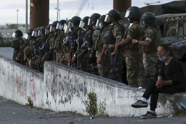 An anti-government protester, right, sits near Lebanese army soldiers standing guard in Beirut, Lebanon, Saturday, June 13, 2020. Lebanese protesters took to the streets in Beirut and other cities in mostly peaceful gatherings against the government, calling for its resignation as the small country sinks deeper into economic distress. (AP Photo/Hassan Ammar)