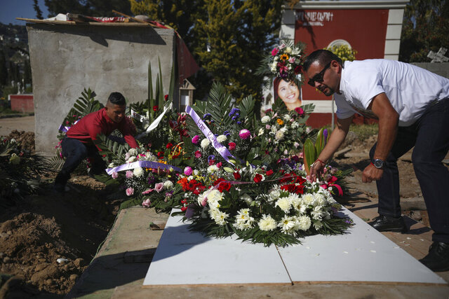 Juan, right, who has been arrested in connection with the disappearance and murder of Marbella Valdez, puts a floral arrangement on her grave, alongside her ex-boyfriend Jairo Solano, during her funeral at a cemetery in Tijuana, Mexico, Friday, Feb. 14, 2020. Juan, who sent her gifts and brought food for her friends, demanded police solve her case after the 20-year-old law student's body, beaten, bound and strangled, was found at a Tijuana garbage dump. Juan has insisted on his innocence. (AP Photo/Emilio Espejel)