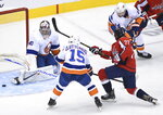 New York Islanders goaltender Semyon Varlamov (40) makes a save on a shot by Washington Capitals right wing T.J. Oshie (77) as Islanders right wing Cal Clutterbuck (15) keeps close during the first period of an NHL Eastern Conference Stanley Cup playoff hockey game in Toronto, Ontario, on Wednesday, Aug. 12, 2020. (Nathan Denette/The Canadian Press via AP)