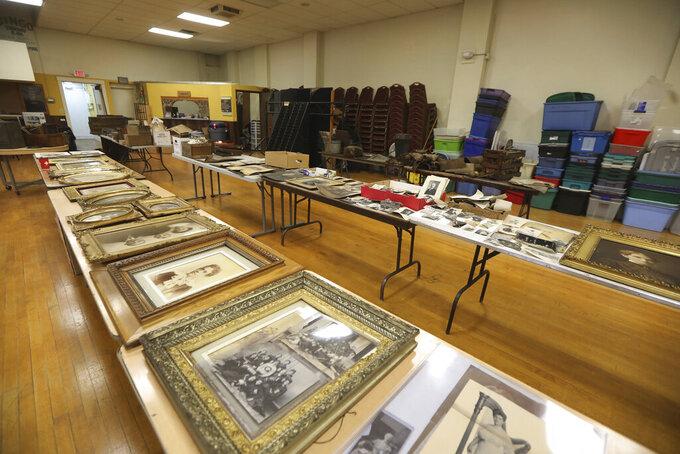 In this Jan. 12, 2021 photo, tables are filled with prints of all sizes that were found in an attic and brought to the antique and auction shop in Canandaigua, N.Y. A rare framed photograph of Susan B. Anthony is being auctioned with a starting price of $5,000. The 20-by-16-inch photo was found in an concealed attic space in a building in Geneva, N.Y, after the property was sold in December. The owner of the building, David Whitcomb, has worked with an antiques dealer to bring some 350 items discovered in the attic to auction. (Tina MacIntyre-Yee/Democrat & Chronicle via AP)