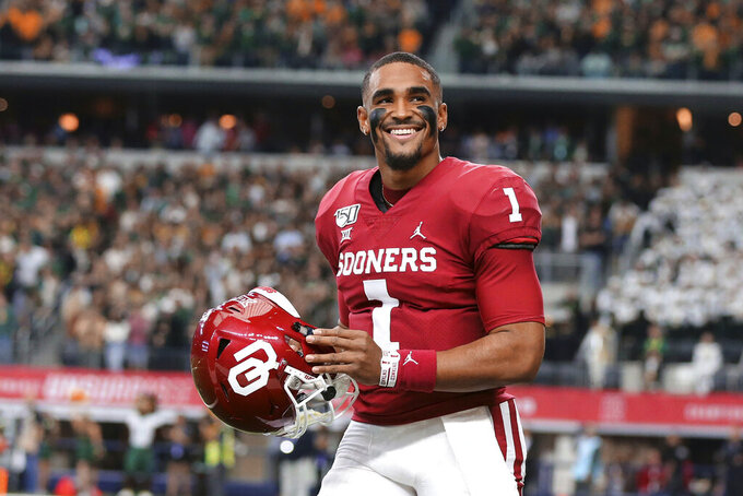 FILE - In this Dec. 9, 2019, file photo, Oklahoma quarterback Jalen Hurts smiles on the sidelines before an NCAA college football game against Baylor for the Big-12 championship, in Arlington, Texas. Hurts, the Heisman Trophy runner-up who once starred for Alabama, is hoping to improve his NFL draft stock at the Senior Bowl. (Rod Aydelotte/Waco Tribune Herald, via AP, File)