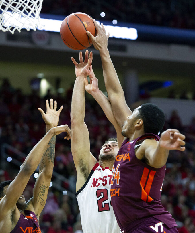 North Carolina State's Devon Daniels, center, has his shot blocked by Virginia Tech's Kerry Blackshear Jr., right, during the first half of an NCAA college basketball game in Raleigh, N.C., Saturday, Feb. 2, 2019. (AP Photo/Ben McKeown)
