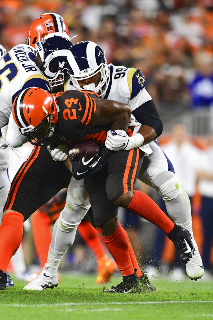 Los Angeles Rams defensive tackle Aaron Donald (99) tackles Cleveland Browns running back Nick Chubb (24) during the first half of an NFL football game, Sunday, Sept. 22, 2019, in Cleveland. (AP Photo/David Dermer)